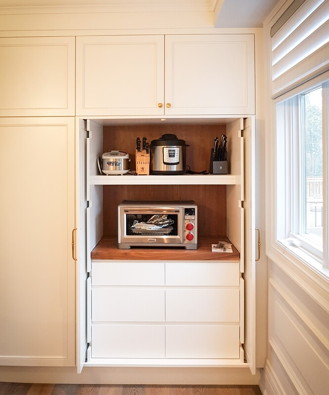 Kitchen appliance cupboard with open-and-slide-back doors and walnut accent finish