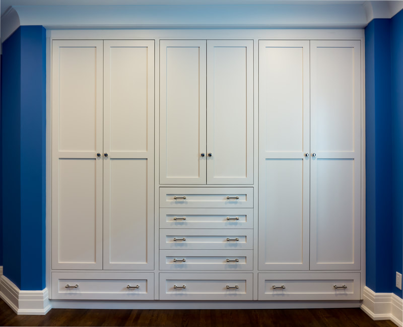 Bedroom closet in white lacquered finish on shaker doors