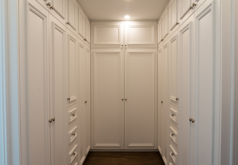 Walk-In closet with applied mouldings on cabinet doors