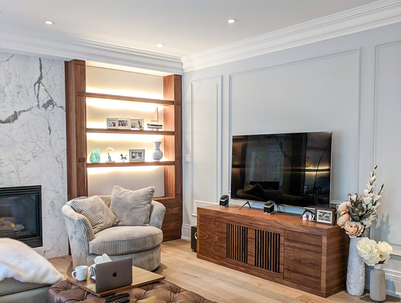 Walnut shelving on either side of fireplace with matching media cabinet